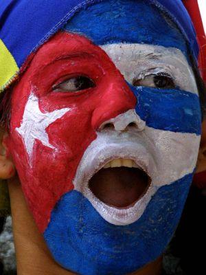 Una mujer con la cara pintada de la bandera cubana frente a la embajada de Cuba en Venezuela. / Juan Barreto (AFP)