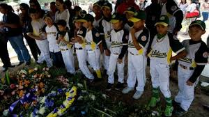 "In this photo taken on Friday, March 14, 2014. Boys that play in a minor league baseball team ""Atleticos de Crimon"" mourn their coach, Guillermo Sanchez after his funeral grave in in Valencia, Venezuela. The people of the poor district of La Isabelica were made to pay for taking to the streets in anti-government protests. More than a dozen masked men on motorcycles roared through, shooting up a barricade and killing a university student and a 42-year-old man painting his house. Fernando Llano / AP Photo"