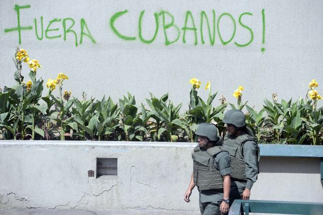 Miembros de la Guardia Nacional patrullan la zona de la plaza Altamira junto a un cartel de rechazo a la presencia de cubanos en el país. JUAN BARRETO / AFP/Getty Images