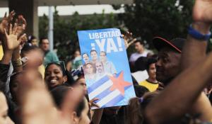 "People cheer for the ""Cuban Five"" while holding a poster of the five Cuban intelligent agents, in Havana December 17, 2014. After 18 months of secret talks facilitated by the Vatican and Canada, Obama and Cuban President Raul Castro agreed by phone on Tuesday on a prisoner exchange and the opening of embassies in each other's countries. Obama said the moves were made possible by Havana's release of American Alan Gross, 65, who had been imprisoned in Cuba for five years. Cuba is also releasing an intelligence agent who spied for the United States and was held for nearly 20 years, and the United States in return freed three Cuban intelligence agents held in the United States. The poster reads ""Freedom now !"". REUTERS"