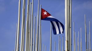 FILE - The Cuban flag flies in front of the U.S. Interests Section in Havana, May 22, 2015.