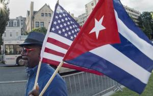 A man waves the US and Cuban flags as he walks in front of the new Cuban Embassy shortly before it's official ceremonial opening July 20, 2015, in Washington, DC. Getty Images/PAUL J. RICHARDS/AFP